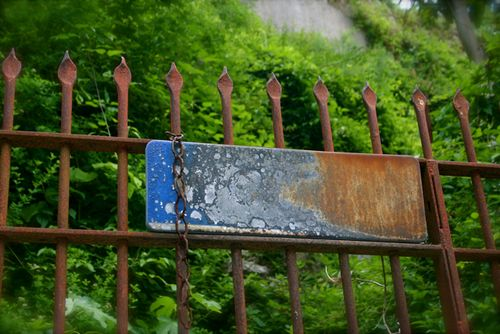 Rusted sign with fence